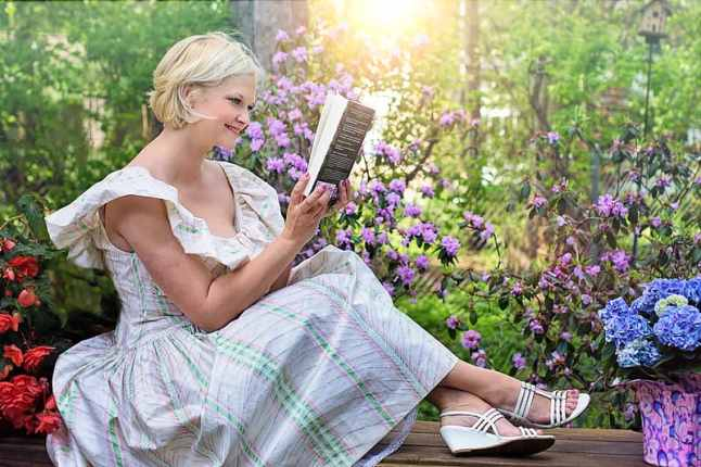 woman-sitting-while-reading-book-outdoors